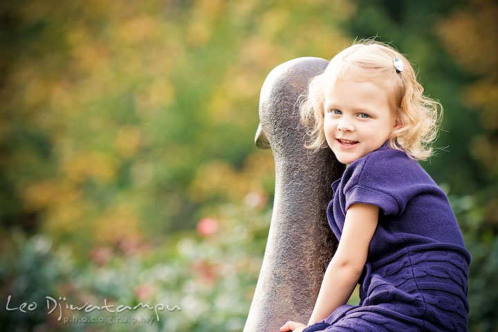 Little blond girl sitting on top of a goose statue. Annapolis Maryland candid lifestyle family portrait photography