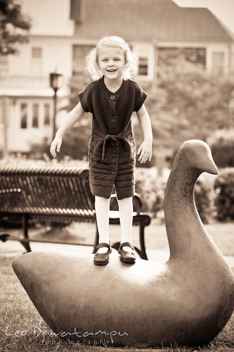 Little girl standing on swan statue. Annapolis Maryland candid lifestyle family portrait photography