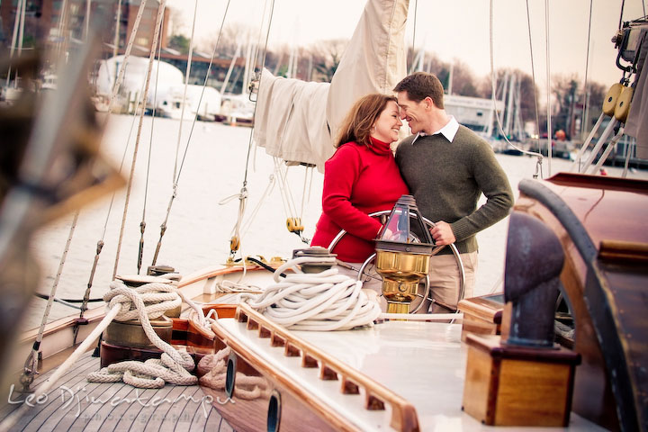 Engaged couple cuddling on a vintage yacht, sailing boat. Urban  city theme engagement session photographer Annapolis MD