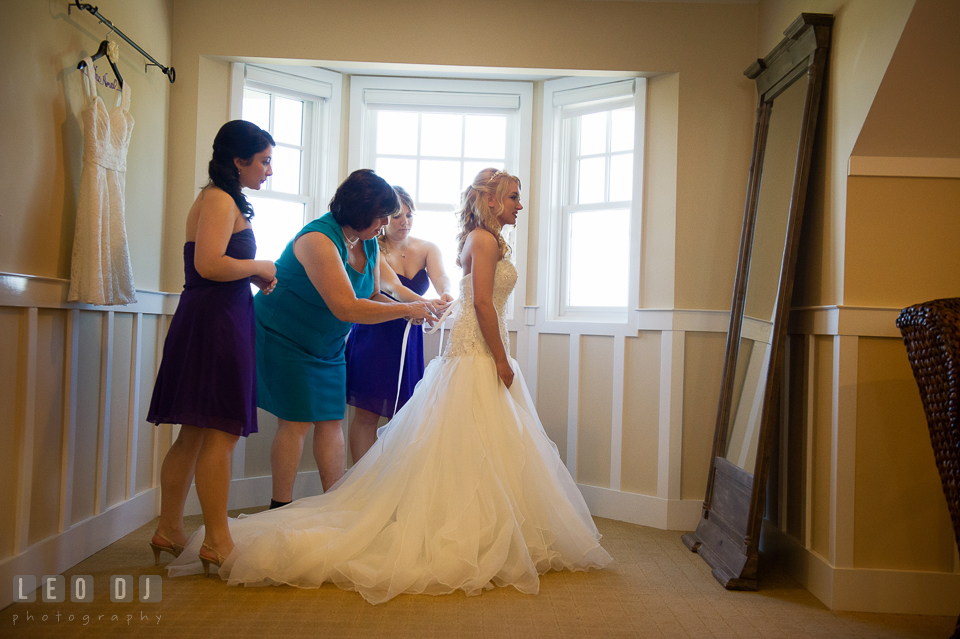 Mother of Bride and Bridesmaids helping Bride getting into dress and lace it up. Kent Island Maryland Chesapeake Bay Beach Club wedding photo, by wedding photographers of Leo Dj Photography. http://leodjphoto.com