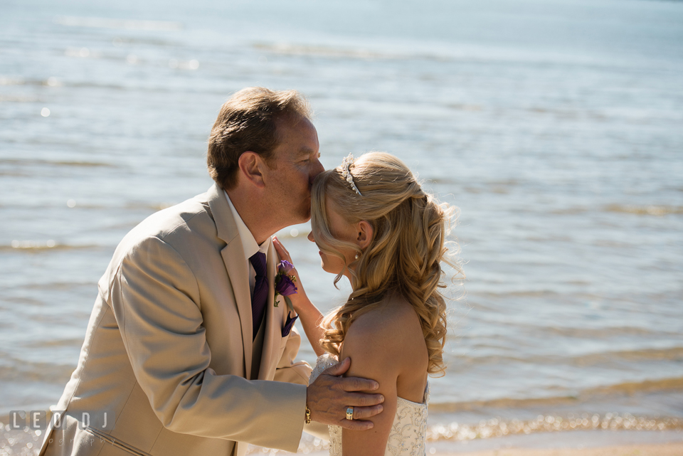 Father of the Bride kissed his daughter's forehead during their first glance. Kent Island Maryland Chesapeake Bay Beach Club wedding photo, by wedding photographers of Leo Dj Photography. http://leodjphoto.com