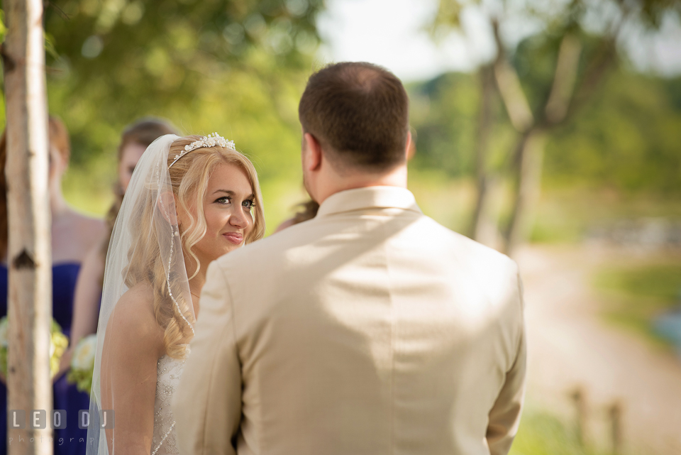 Bride smiling while glancing at Groom during their wedding vows. Kent Island Maryland Chesapeake Bay Beach Club wedding photo, by wedding photographers of Leo Dj Photography. http://leodjphoto.com