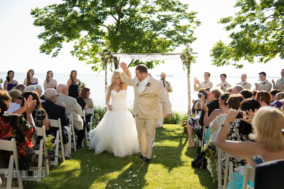 Bride and Groom raised their arms during the recessional at the ceremony. Kent Island Maryland Chesapeake Bay Beach Club wedding photo, by wedding photographers of Leo Dj Photography. http://leodjphoto.com