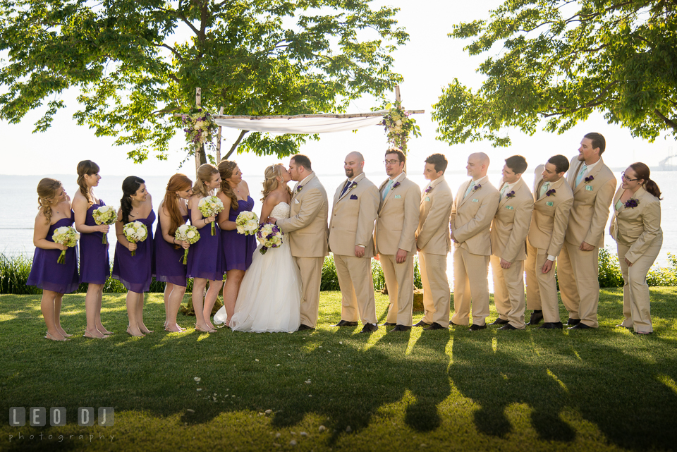 Bride and Groom kissing while bridesmaids and groomsman looked. Kent Island Maryland Chesapeake Bay Beach Club wedding photo, by wedding photographers of Leo Dj Photography. http://leodjphoto.com