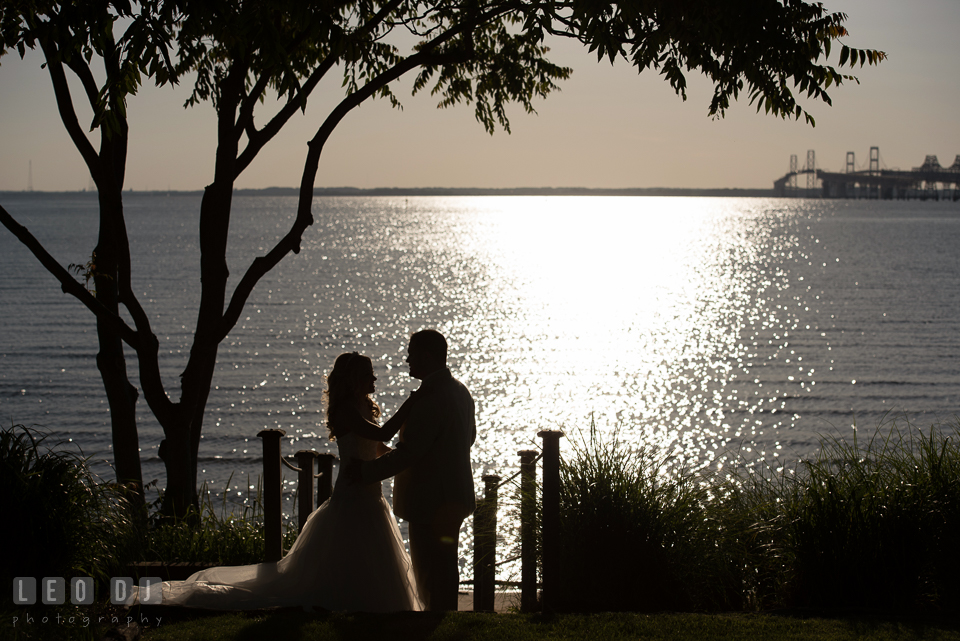 Bride and Groom in a silhouette against a water view of the Chesapeake Bay and the Bay Bridge. Kent Island Maryland Chesapeake Bay Beach Club wedding photo, by wedding photographers of Leo Dj Photography. http://leodjphoto.com