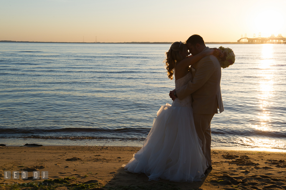 Silhouette of Bride and Groom hugging on the beach of Chesapeake Bay during sunset. Kent Island Maryland Chesapeake Bay Beach Club wedding photo, by wedding photographers of Leo Dj Photography. http://leodjphoto.com