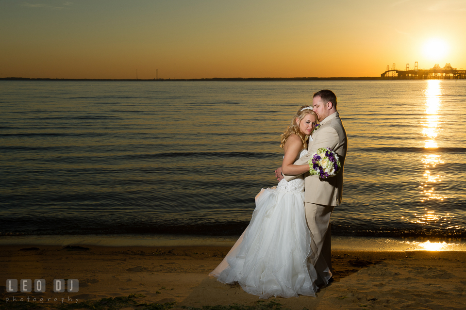 Groom hugging Bride on the beach of Chesapeake Bay during sunset. Kent Island Maryland Chesapeake Bay Beach Club wedding photo, by wedding photographers of Leo Dj Photography. http://leodjphoto.com