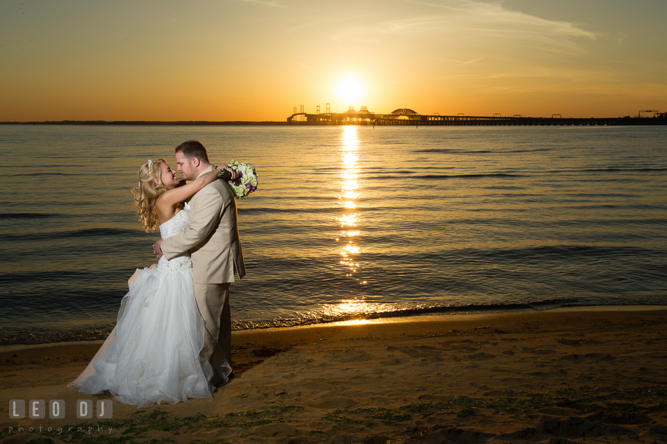 Bride and Groom smiling and looking at each other with background view of the Chesapeake Bay and Bay Bridge at sunset. Kent Island Maryland Chesapeake Bay Beach Club wedding photo, by wedding photographers of Leo Dj Photography. http://leodjphoto.com