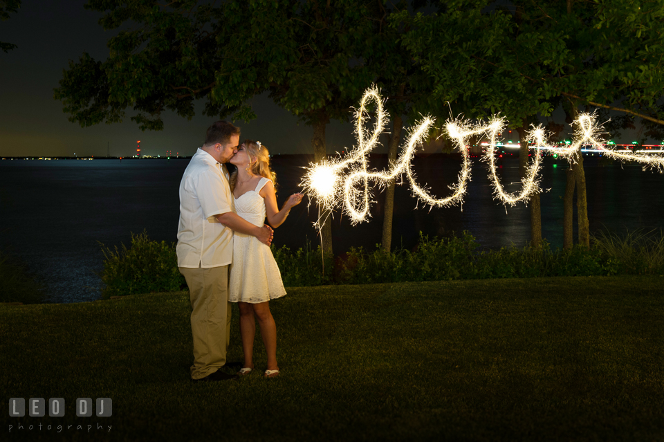 Bride and Groom kissing with sparklers writing Love. Kent Island Maryland Chesapeake Bay Beach Club wedding photo, by wedding photographers of Leo Dj Photography. http://leodjphoto.com