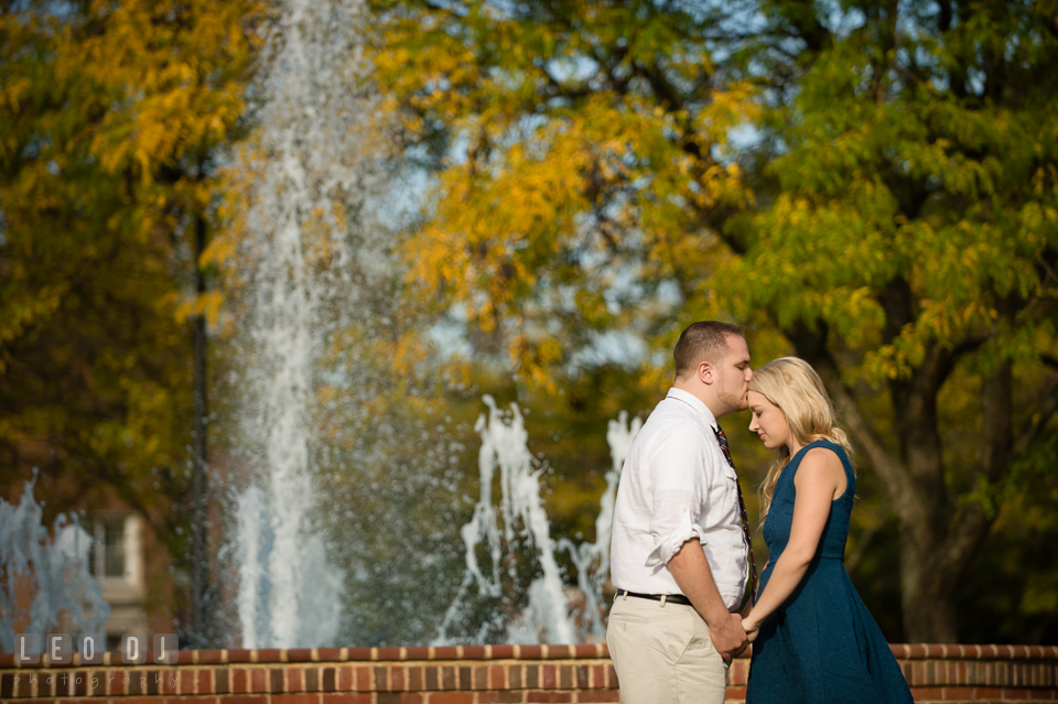 Engaged girl by the water fountain kissed on the forehead by her fiancé. Gettysburg PA pre-wedding engagement photo session, by wedding photographers of Leo Dj Photography. http://leodjphoto.com