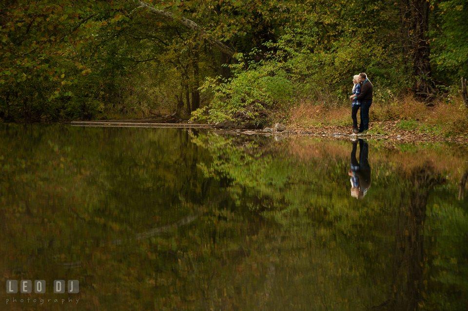 Engaged couple cuddling by the pond in the forest. Gettysburg PA pre-wedding engagement photo session, by wedding photographers of Leo Dj Photography. http://leodjphoto.com