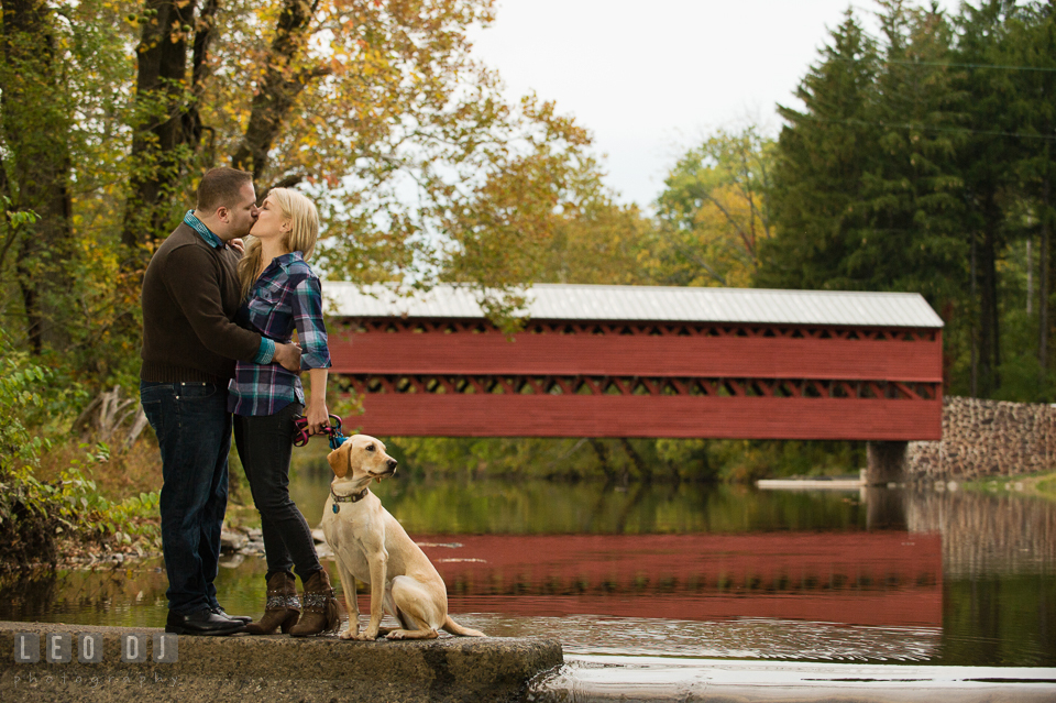 Engaged couple kissing by the river by the Sachs Covered Bridge with their labrador dog. Gettysburg PA pre-wedding engagement photo session, by wedding photographers of Leo Dj Photography. http://leodjphoto.com