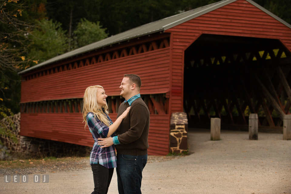 Engaged girl and her fiance embracing together and laughing by the Sachs Covered Bridge. Gettysburg PA pre-wedding engagement photo session, by wedding photographers of Leo Dj Photography. http://leodjphoto.com