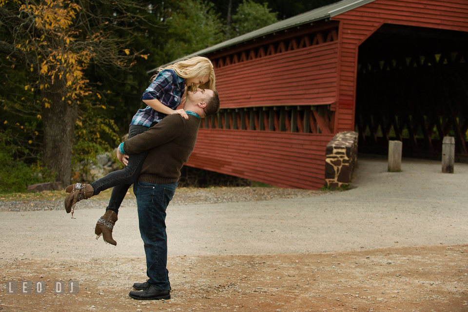 Engaged man lift up his fiancee laughing and almost kissed by the Sachs Covered Bridge. Gettysburg PA pre-wedding engagement photo session, by wedding photographers of Leo Dj Photography. http://leodjphoto.com