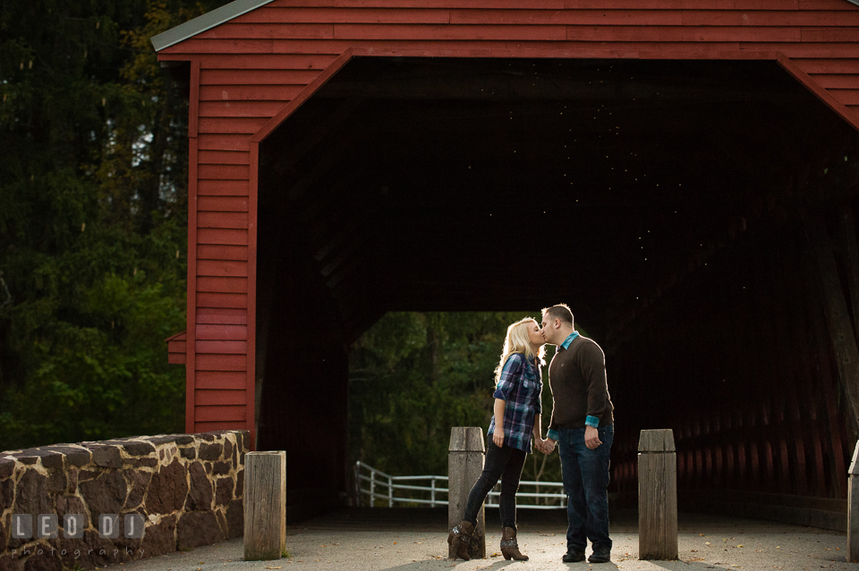 Engaged couple by the Sachs Covered Bridge holding hands and kissing. Gettysburg PA pre-wedding engagement photo session, by wedding photographers of Leo Dj Photography. http://leodjphoto.com
