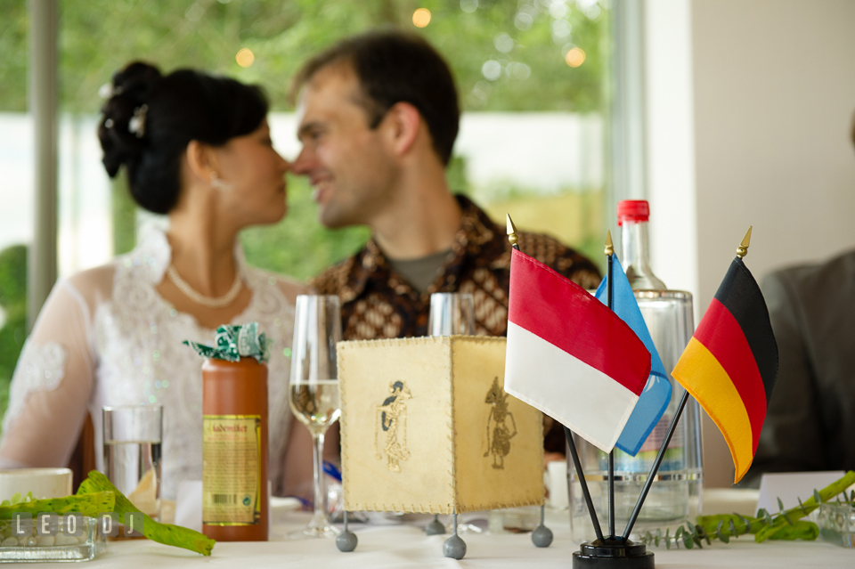 Tender moments between the Bride and Groom at their table with Indonesian and German flags. Landgrafen Restaurant, Jena, Germany, wedding reception and ceremony photo, by wedding photographers of Leo Dj Photography. http://leodjphoto.com
