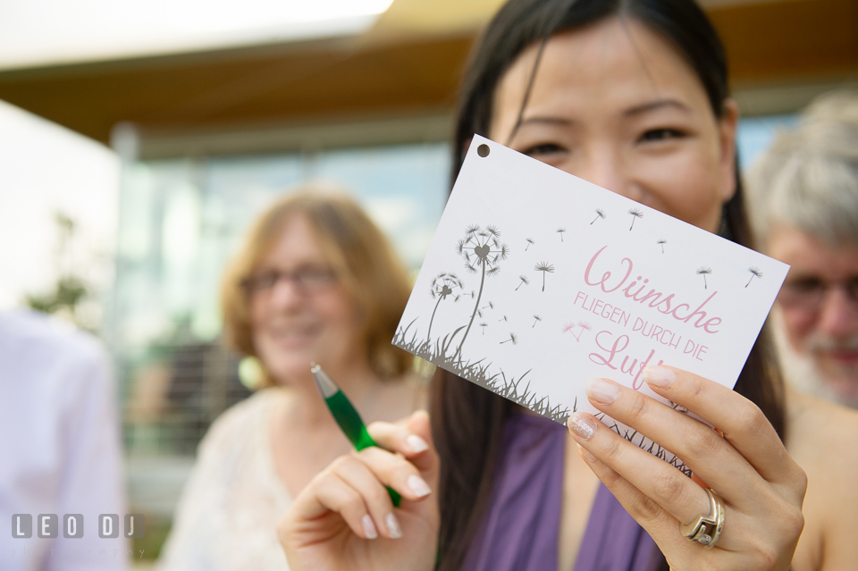 A guest showing the front of the postcard to be flown. Landgrafen Restaurant, Jena, Germany, wedding reception and ceremony photo, by wedding photographers of Leo Dj Photography. http://leodjphoto.com