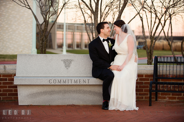 Bride sitting on lap of Groom whom sitting on the bench with Commitment inscription at the USNA. Historic Inns of Annapolis, Governor Calvert House wedding Maryland, by wedding photographers of Leo Dj Photography. http://leodjphoto.com