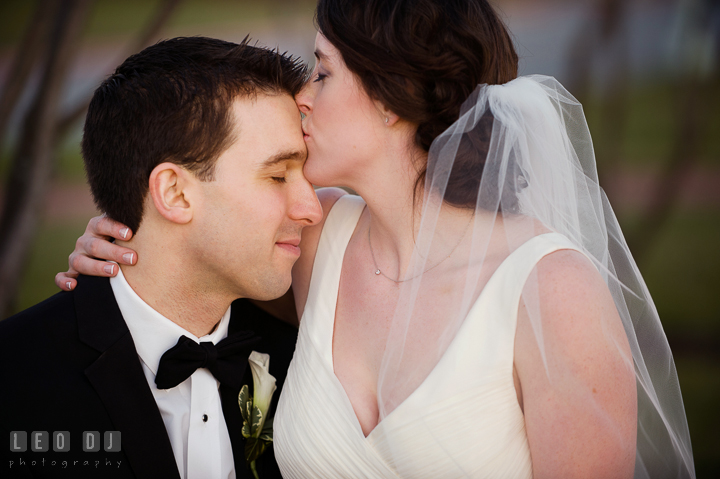 Bride kissing Groom's forehead at the United States Naval Academy campus. Historic Inns of Annapolis, Governor Calvert House wedding Maryland, by wedding photographers of Leo Dj Photography. http://leodjphoto.com