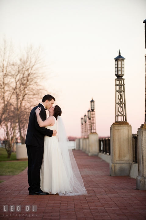 Bride and Groom along the waters of the US Naval Academy campus kissing. Historic Inns of Annapolis, Governor Calvert House wedding Maryland, by wedding photographers of Leo Dj Photography. http://leodjphoto.com