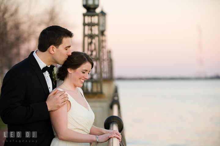 Groom kiss Bride while overlooking the water view at the US Naval Academy pier. Historic Inns of Annapolis, Governor Calvert House wedding Maryland, by wedding photographers of Leo Dj Photography. http://leodjphoto.com
