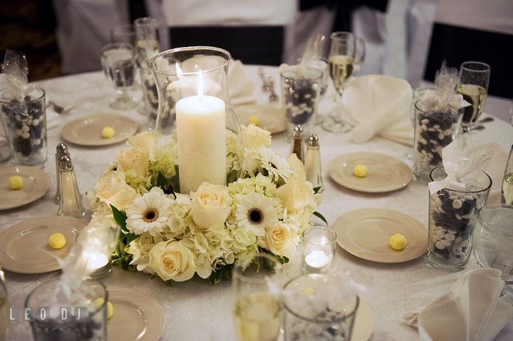 White flower table centerpiece with candle by Fantastic Flowers and M&M wedding favors. Historic Inns of Annapolis, Governor Calvert House wedding Maryland, by wedding photographers of Leo Dj Photography. http://leodjphoto.com