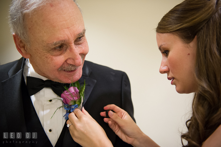 Bride's sister and Maid of Honor putting on boutonniere for Father. Falls Church Virginia 2941 Restaurant wedding ceremony photo, by wedding photographers of Leo Dj Photography. http://leodjphoto.com