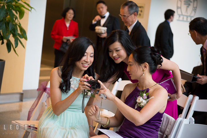 Groom's sisters and sister-in-law looking at photo result on camera. Falls Church Virginia 2941 Restaurant wedding ceremony photo, by wedding photographers of Leo Dj Photography. http://leodjphoto.com