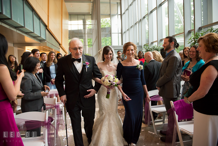 Bride walking down the isle during procession, escorted by Father and Mother of Bride. Falls Church Virginia 2941 Restaurant wedding ceremony photo, by wedding photographers of Leo Dj Photography. http://leodjphoto.com