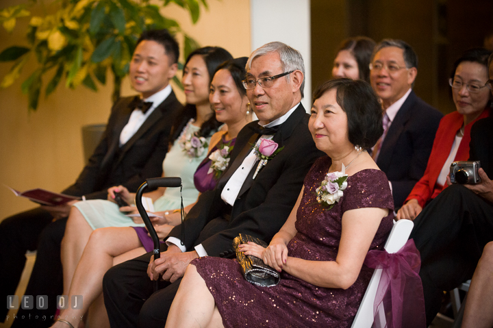 Groom's parents and siblings smiling listening to Bride and Groom's vows. Falls Church Virginia 2941 Restaurant wedding ceremony photo, by wedding photographers of Leo Dj Photography. http://leodjphoto.com