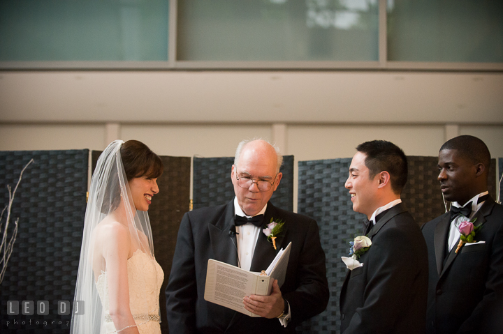 Bride and Groom smiling to each other during the ceremony. Falls Church Virginia 2941 Restaurant wedding ceremony photo, by wedding photographers of Leo Dj Photography. http://leodjphoto.com