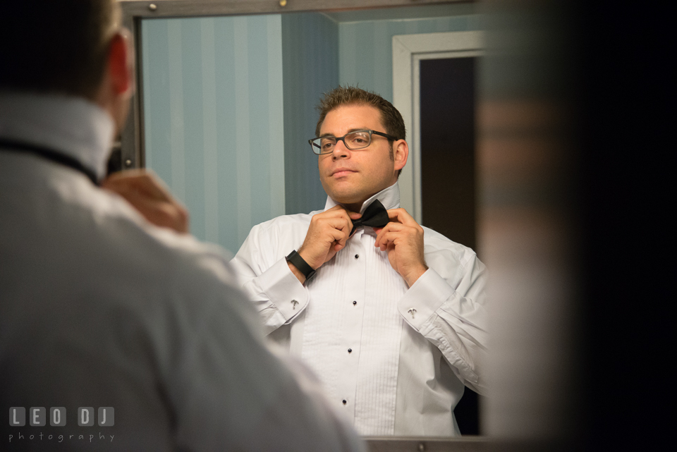 Groom looking in the mirror fixing his bow tie. Loews Annapolis Hotel Maryland wedding, by wedding photographers of Leo Dj Photography. http://leodjphoto.com