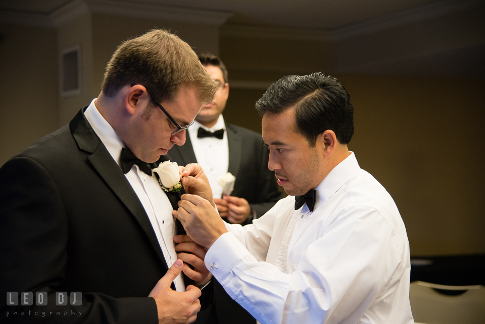 Groomsmen helping Groom put on boutonniere. Loews Annapolis Hotel Maryland wedding, by wedding photographers of Leo Dj Photography. http://leodjphoto.com