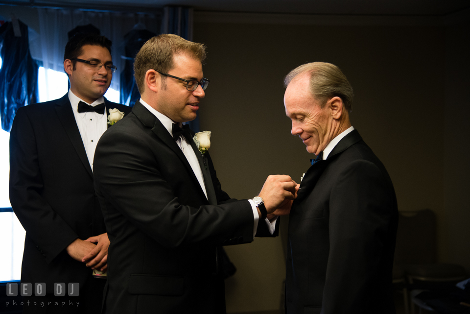 Groom helping Father of Bride put on boutonniere. Loews Annapolis Hotel Maryland wedding, by wedding photographers of Leo Dj Photography. http://leodjphoto.com