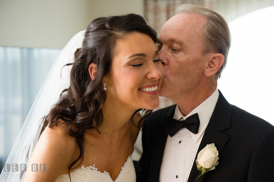Father of Bride kissed daughter on cheek during first look with Dad. Loews Annapolis Hotel Maryland wedding, by wedding photographers of Leo Dj Photography. http://leodjphoto.com