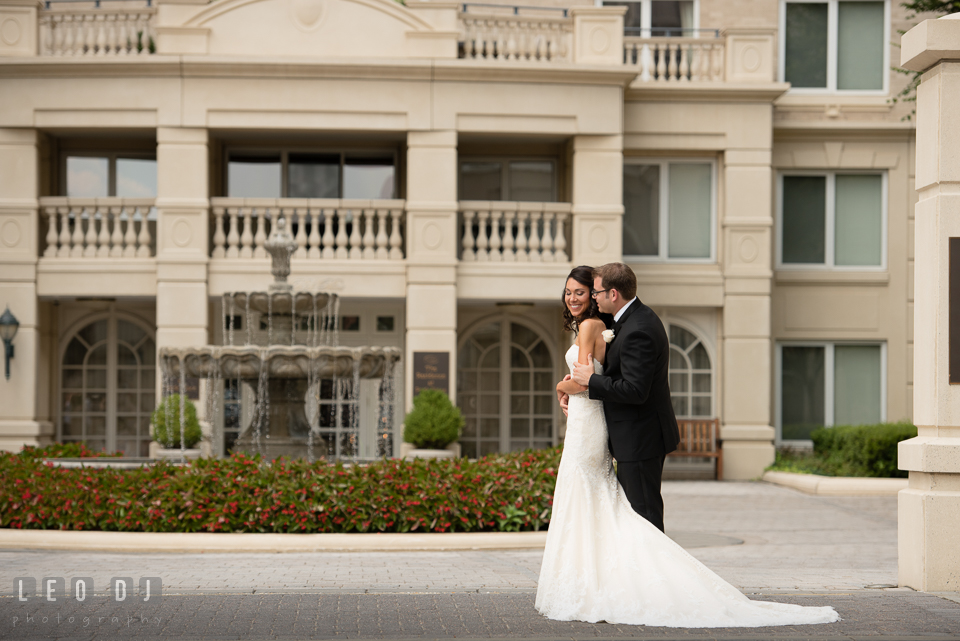 Groom hugging Bride in front of a water fountain. Loews Annapolis Hotel Maryland wedding, by wedding photographers of Leo Dj Photography. http://leodjphoto.com