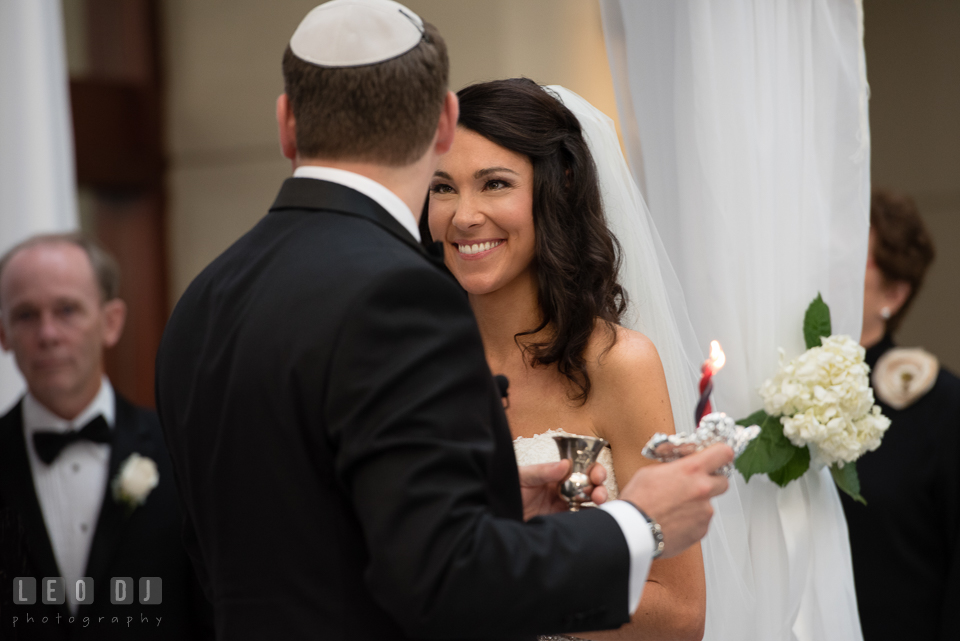 Bride smiling as Groom lift up candle and wine cup, traditional Jewish wedding ceremony. Loews Annapolis Hotel Maryland wedding, by wedding photographers of Leo Dj Photography. http://leodjphoto.com