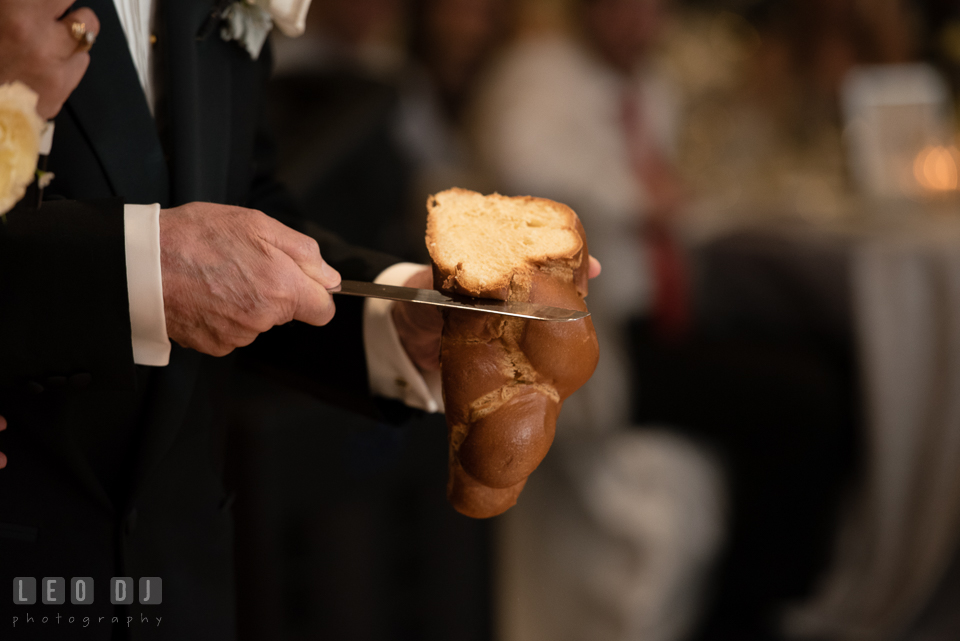 Grandfather cutting bread during blessing over challah. Loews Annapolis Hotel Maryland wedding, by wedding photographers of Leo Dj Photography. http://leodjphoto.com
