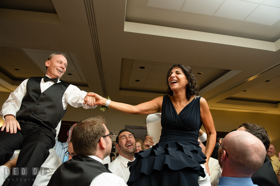 Father and Mother of Bride holding hands while raised up during Hora dance. Loews Annapolis Hotel Maryland wedding, by wedding photographers of Leo Dj Photography. http://leodjphoto.com