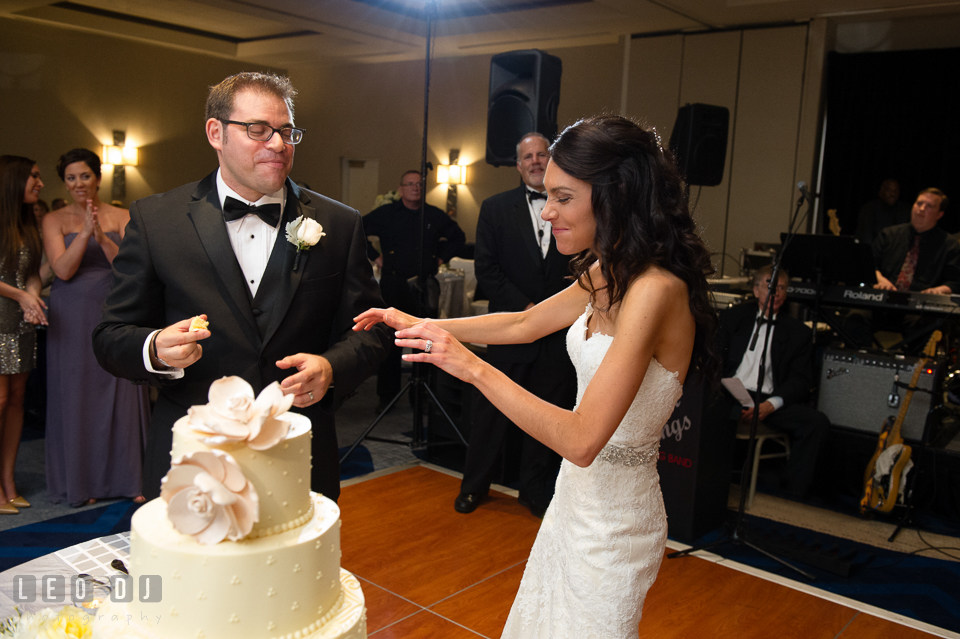 Bride and Groom teasing each other during cake cutting. Loews Annapolis Hotel Maryland wedding, by wedding photographers of Leo Dj Photography. http://leodjphoto.com