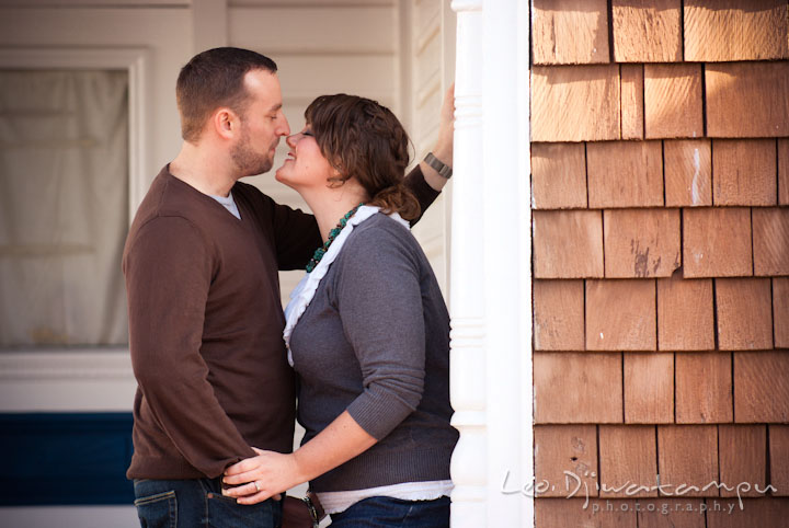 Engaged guy cuddling with his fiancée. Pre-wedding or engagement photo session at Annapolis city harbor, Maryland, Eastern Shore, by wedding photographers of Leo Dj Photography.