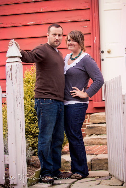 Engaged couple posing by a picket fence gate. Pre-wedding or engagement photo session at Annapolis city harbor, Maryland, Eastern Shore, by wedding photographers of Leo Dj Photography.