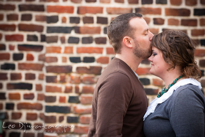 Engaged guy kissed his fiancée's forehead. Pre-wedding or engagement photo session at Annapolis city harbor, Maryland, Eastern Shore, by wedding photographers of Leo Dj Photography.