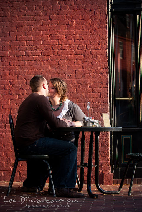 Engaged guy and girl sitting at an outside restaurant table and kissing. Pre-wedding or engagement photo session at Annapolis city harbor, Maryland, Eastern Shore, by wedding photographers of Leo Dj Photography.