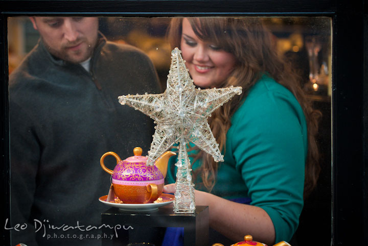 Engaged girl and her fiance browsing Christmas ornament and tea pot. Pre-wedding or engagement photo session at Annapolis city harbor, Maryland, Eastern Shore, by wedding photographers of Leo Dj Photography.
