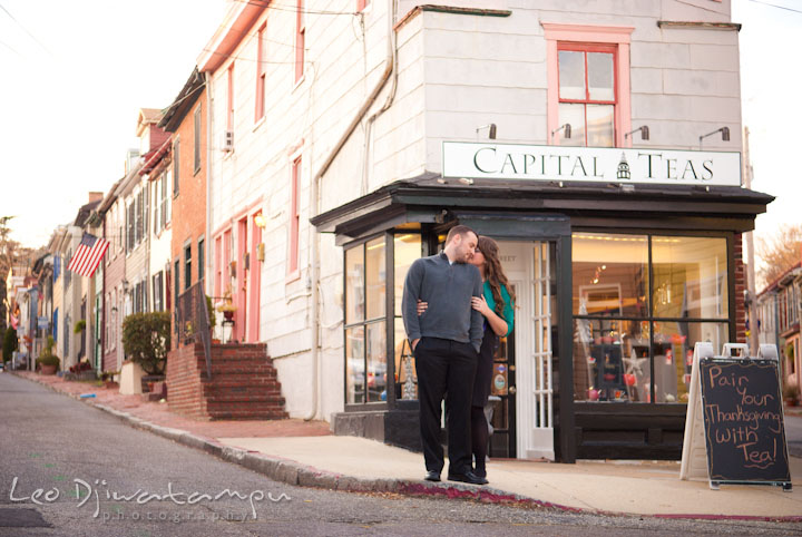 Engaged girl hugging her fiance in front of a tea shop. Pre-wedding or engagement photo session at Annapolis city harbor, Maryland, Eastern Shore, by wedding photographers of Leo Dj Photography.