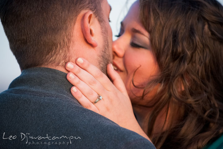 Engaged guy and girl almost kissed and showing engagement ring. Pre-wedding or engagement photo session at Annapolis city harbor, Maryland, Eastern Shore, by wedding photographers of Leo Dj Photography.
