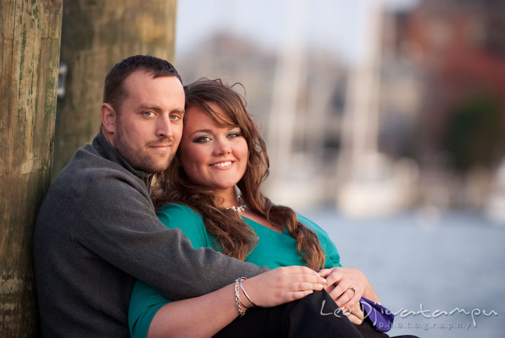 Engaged couple cuddling and smiling. Pre-wedding or engagement photo session at Annapolis city harbor, Maryland, Eastern Shore, by wedding photographers of Leo Dj Photography.