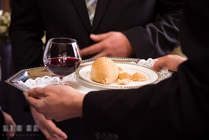 Communion of husband and wife with wine and bread. The Ballroom at The Chesapeake Inn wedding ceremony photos, Chesapeake City, Maryland by photographers of Leo Dj Photography.