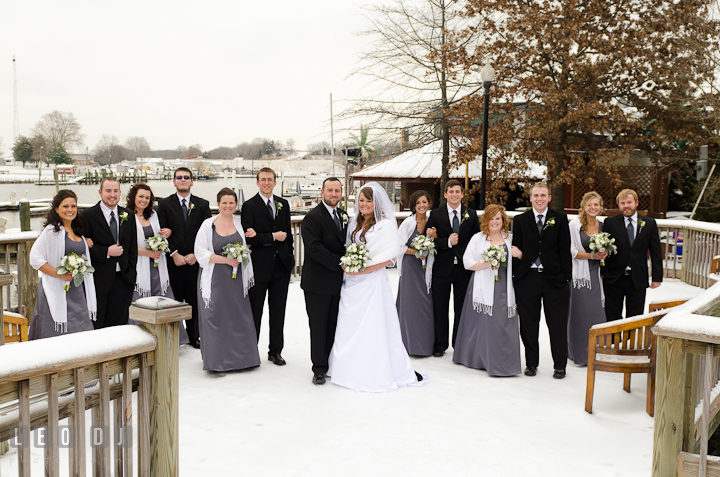 Bride, Groom and the Bridal Party posing on a deck covered with snow. The Ballroom at The Chesapeake Inn wedding ceremony photos, Chesapeake City, Maryland by photographers of Leo Dj Photography.